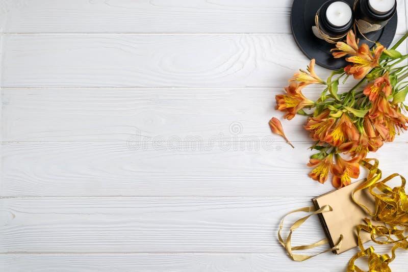 Composição com as flores do saco do presente e as velas do fundo dos presentes com espaço para o texto fotografia de stock