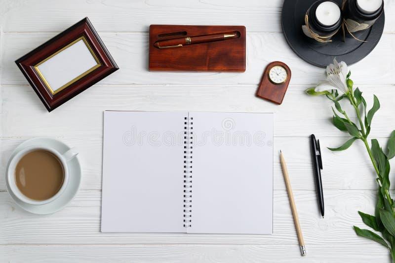 Composição com as flores estacionárias do café do lápis da pena do caderno da educação do escritório fotografia de stock