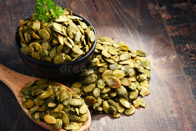Composição com a bacia de sementes de abóbora na tabela de madeira foto de stock royalty free