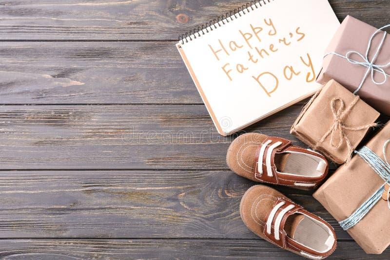 Composição com caixas de presente, caderno e sapatas de bebê no fundo de madeira Celebra??o feliz do dia de pai imagens de stock royalty free