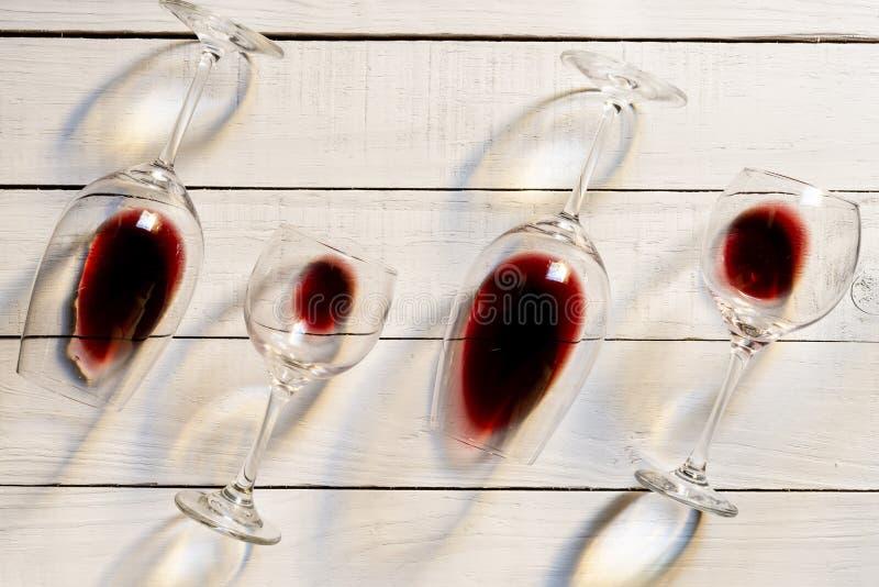 Composição com diversos vidros de vinho usados com líquido restante sobre o fundo de madeira Vista superior com espaço da cópia imagem de stock