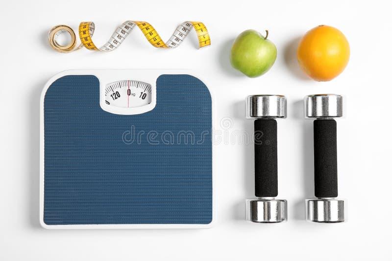 Composição com escalas, frutos, fita métrica e pesos no fundo branco imagens de stock royalty free