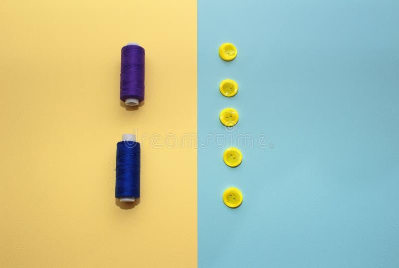 Composição com escuro - linhas e acessórios azuis costurar no fundo amarelo foto de stock