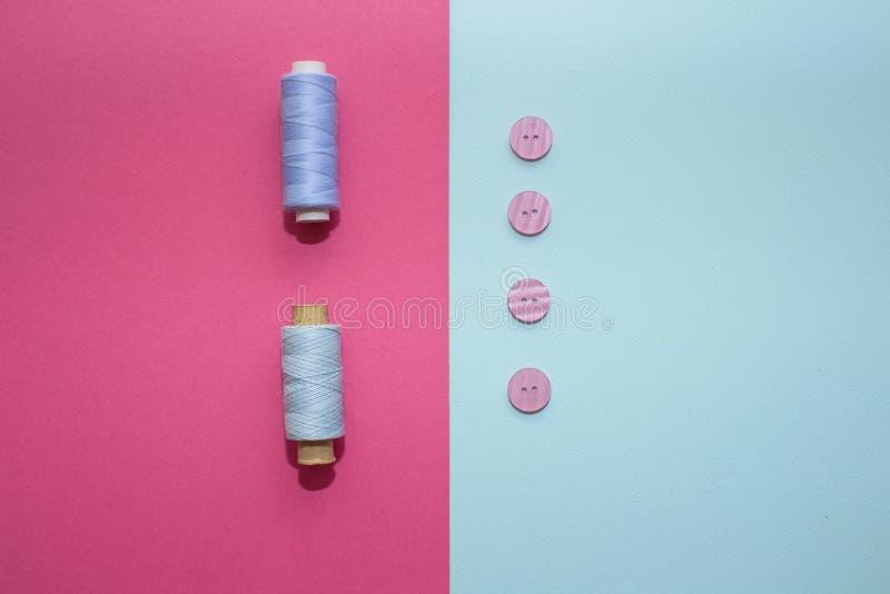 Composição com linhas e os acessórios azuis costurar no fundo cor-de-rosa imagens de stock royalty free