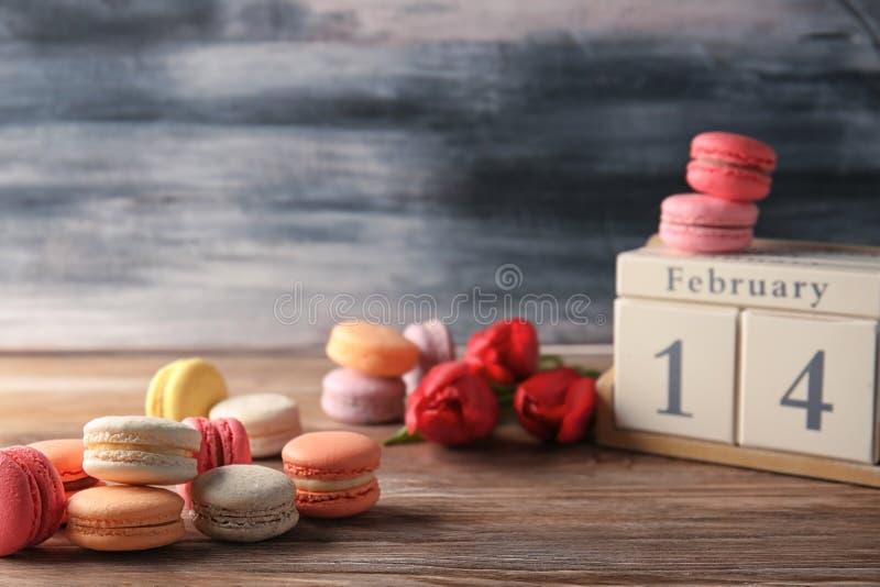 Composição com macarons e calendário de bloco na tabela imagens de stock
