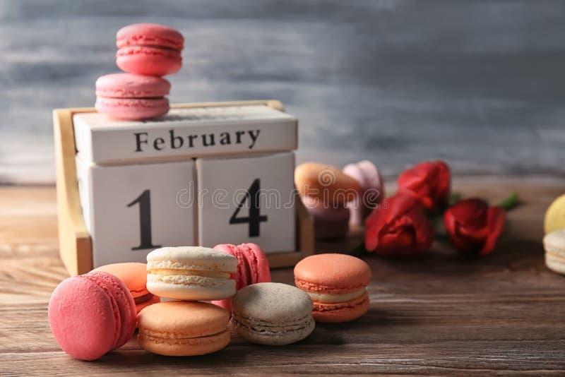 Composição com macarons e calendário de bloco na tabela foto de stock