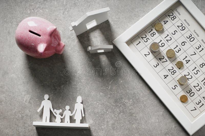 Composição com modelo do mealheiro, do calendário e da casa no fundo cinzento Conceito do dinheiro de salvamento para comprar a c imagens de stock royalty free