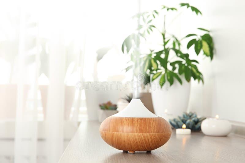 Composição com o difusor moderno do óleo essencial na prateleira de madeira dentro imagens de stock