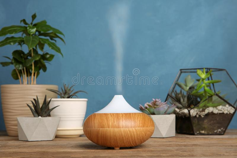 Composição com o difusor moderno do óleo essencial na tabela de madeira contra o fundo azul fotos de stock