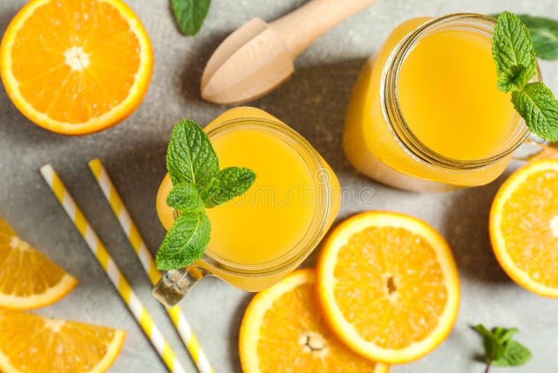 Composição com partes alaranjadas, hortelã, tubules, o juicer de madeira e os frascos de vidro com suco de laranja fresco no fund imagem de stock royalty free