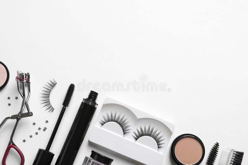 Composição com pestanas falsas e outros produtos de composição no fundo branco imagens de stock royalty free
