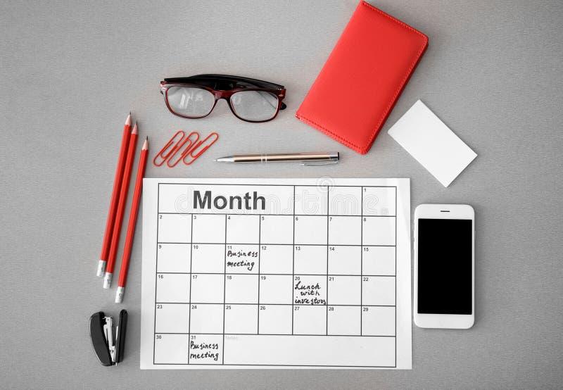 Composição com telefone celular, calendário de nomeação e artigos de papelaria no fundo claro foto de stock