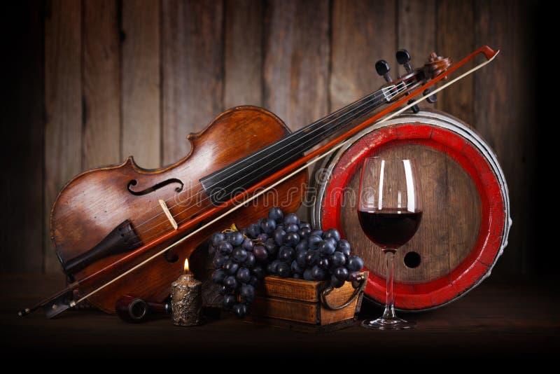 Composição com uva vermelha, vinho, violino e tambor fotografia de stock