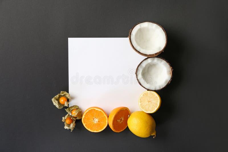 Composição com vários frutos exóticos deliciosos e cartão vazio no fundo escuro fotografia de stock royalty free