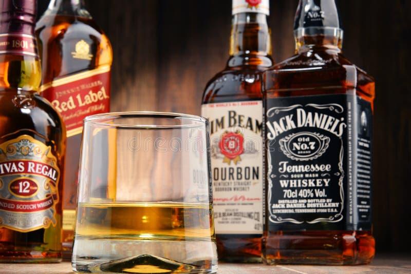 Composição com vidro e garrafas de diversos tipos do uísque fotografia de stock