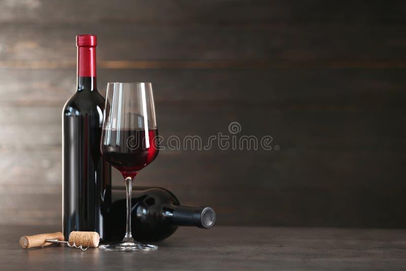 Composição com vidro e garrafas do vinho tinto na tabela imagem de stock
