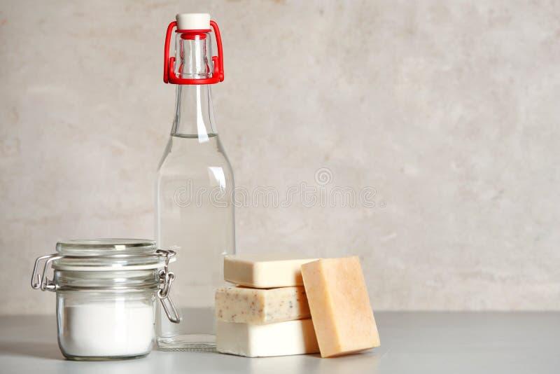 Composição com vinagre, bicarbonato de sódio e barras do sabão para limpar na tabela fotos de stock royalty free