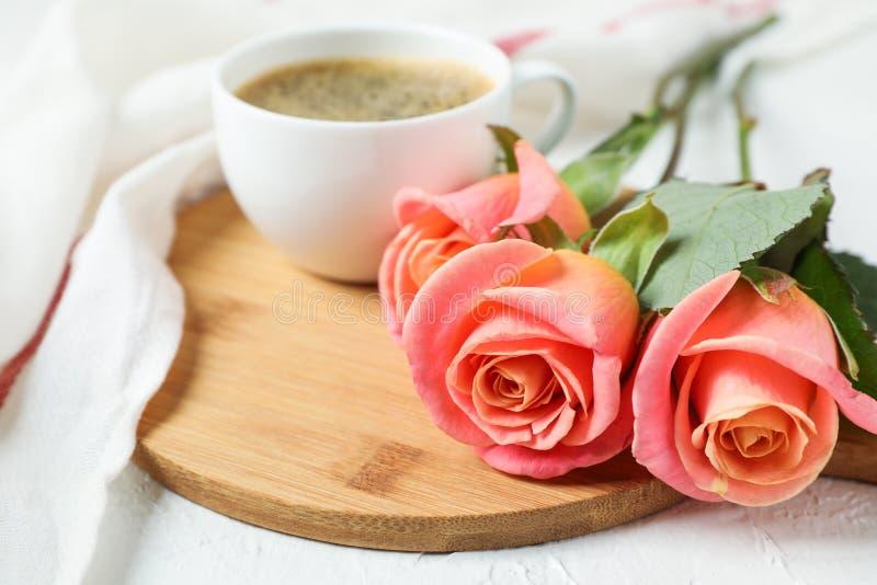 Composição com xícara de café, rosas e toalha de cozinha no fundo branco imagem de stock royalty free