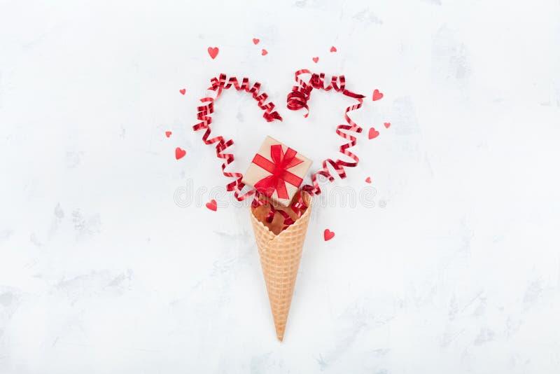 Composição criativa do dia de Valentim com cone do waffle, presente ou caixa e corações atuais na opinião superior do fundo branc imagem de stock