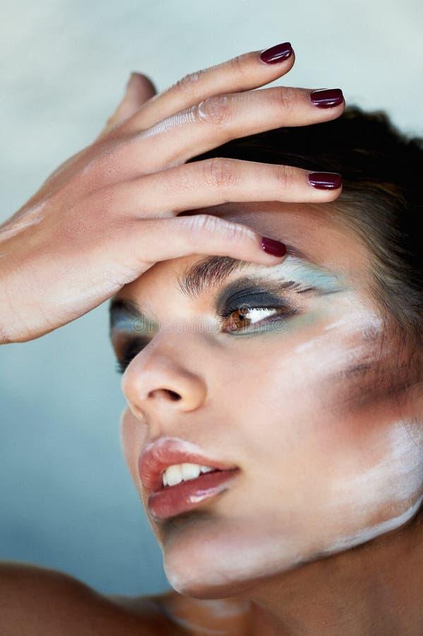 Composição criativa, manchas da pintura na cara A menina toca em sua cara com seus dedos Dedos longos bonitos imagens de stock royalty free