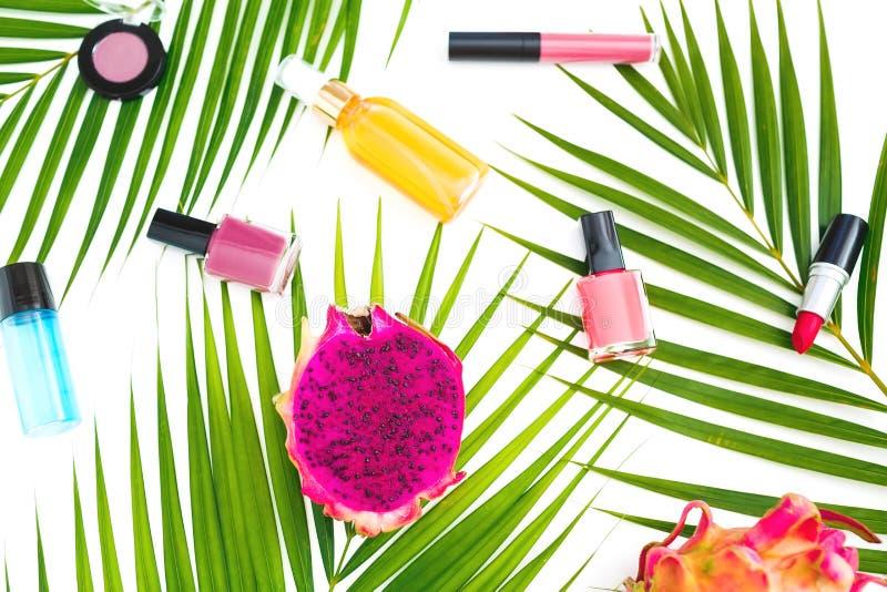 Composição da beleza de frutos, de folhas de palmeira e de cosméticos do dragão no fundo branco Configuração lisa, vista superior imagens de stock royalty free