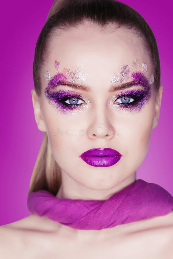 Composição da beleza Composição roxa e pregos brilhantes coloridos Retrato bonito do close-up da menina imagens de stock