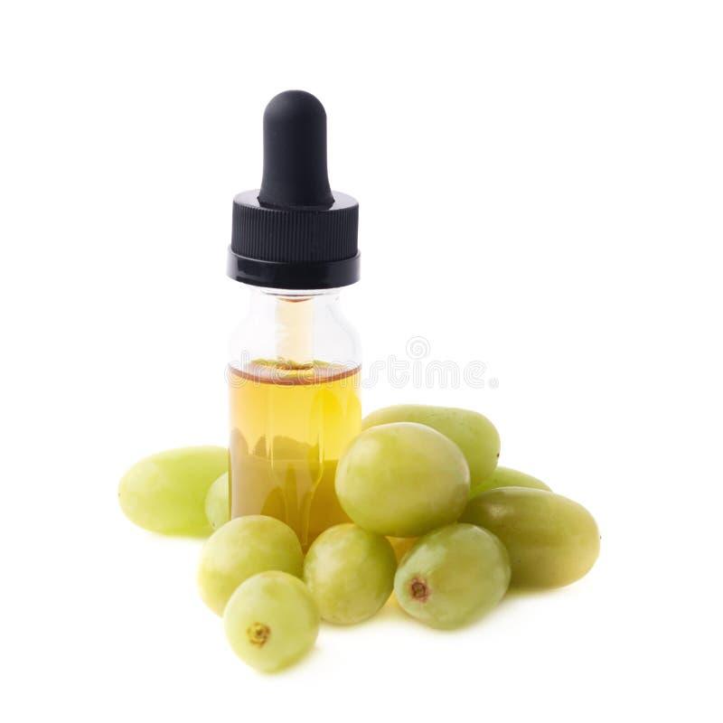 Composição da essência do óleo de semente da uva isolada fotografia de stock