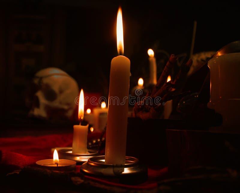 Composição da feitiçaria com velas e crânio imagem de stock