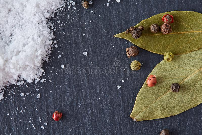Composição da folha do louro de baía com grão de pimenta e sal no fundo escuro, vista superior, close-up, foco seletivo foto de stock