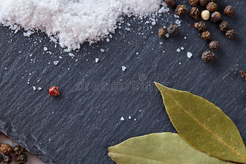 Composição da folha do louro de baía com o grão de pimenta e o sal isolados no fundo escuro, vista superior, close-up, foco selet imagens de stock royalty free