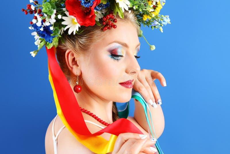 Composição da mulher do retrato com as flores no fundo azul fotos de stock royalty free