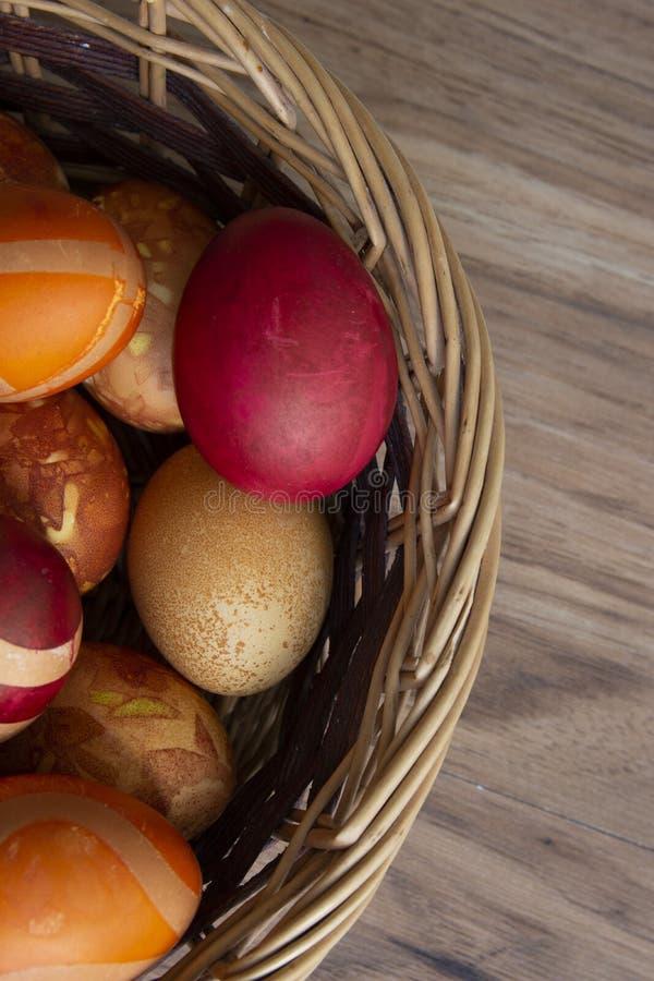 Composição da Páscoa com ovos da páscoa em uma cesta no fundo de madeira da cor foto de stock royalty free