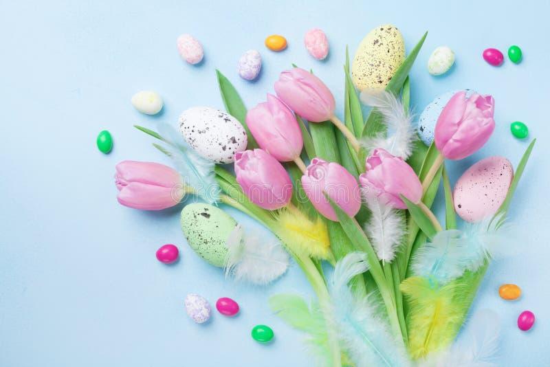Composição da Páscoa com ovos, flores da mola, penas e os doces coloridos na opinião de tampo da mesa azul imagens de stock