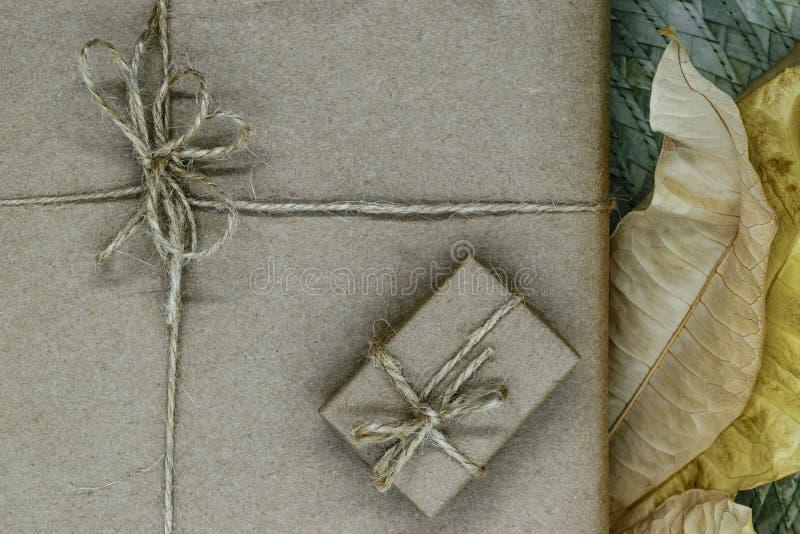 Composição das caixas de presente envolvidas no papel bege e empacotadas com fitas Decorado com folhas secas imagens de stock
