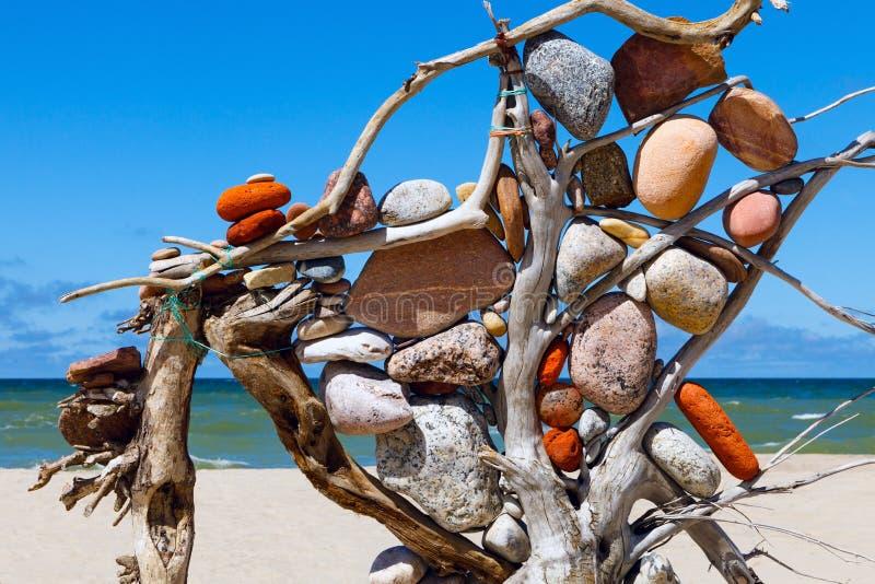Composição das pedras e da árvore seca no fundo do mar Zen da rocha na praia imagem de stock royalty free
