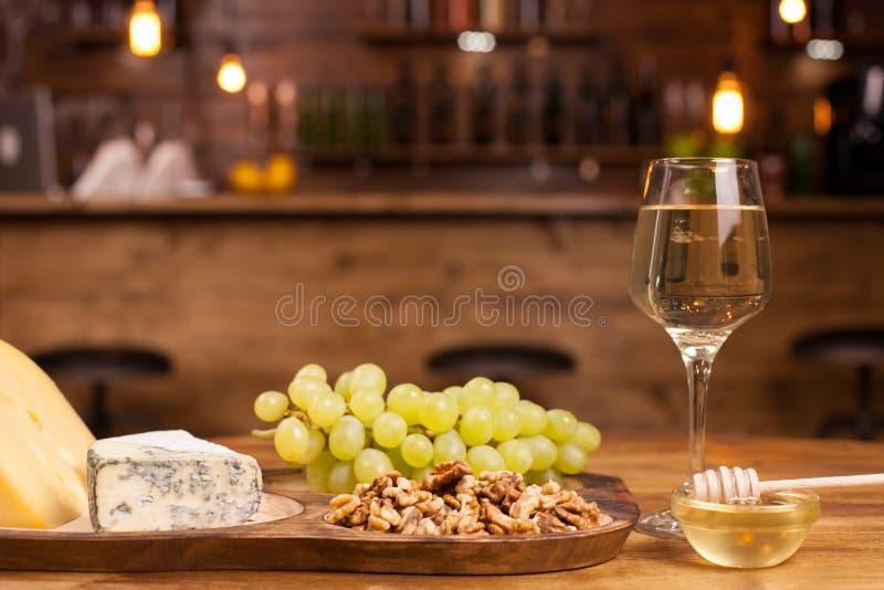 Composi??o de alimento com os petiscos varisious para o vinho branco em uma tabela de madeira fotos de stock