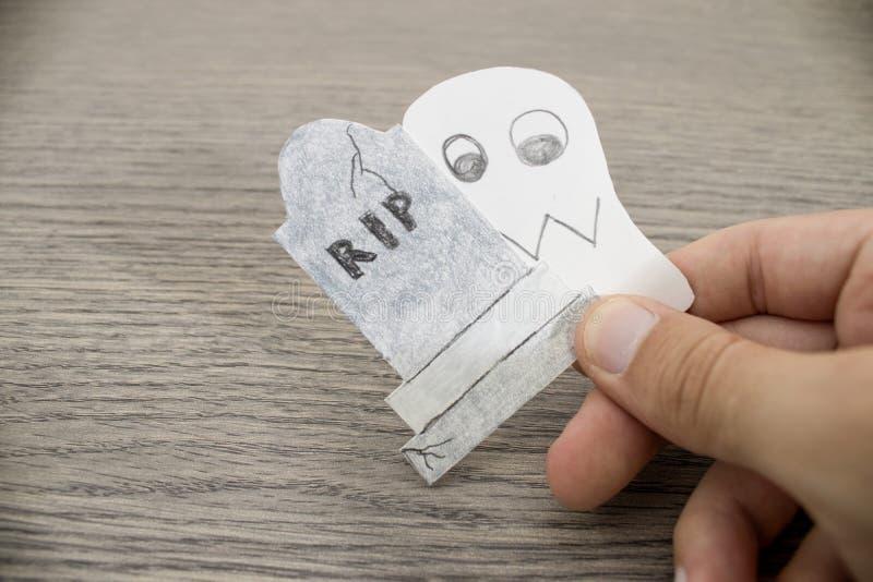 A composição de Dia das Bruxas, mão está guardando um fantasma e uma lápide o foto de stock