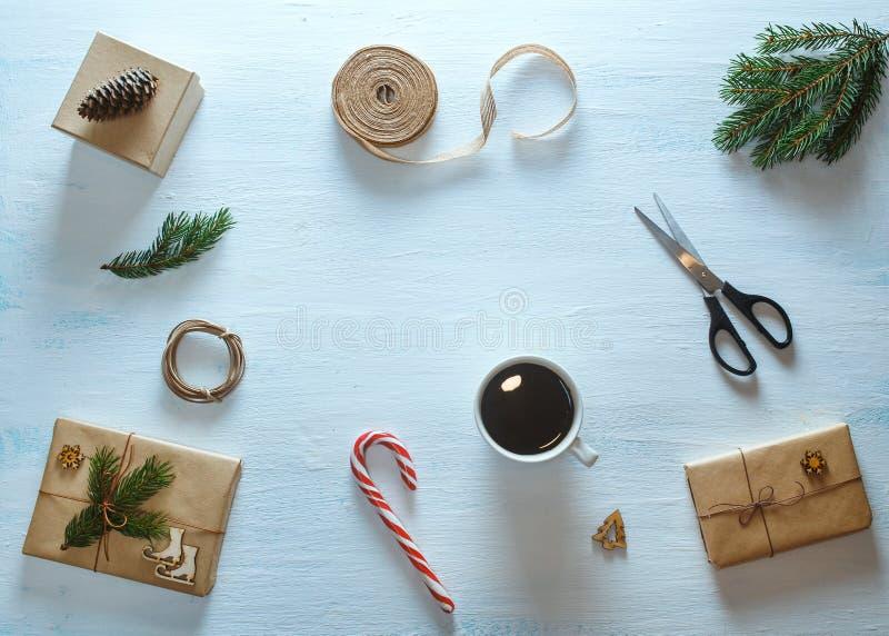 Composição de empacotamento do presente do Natal Os presentes do Natal, copo do chá, doces, abeto ramificam, tesouras, fita Confi fotos de stock