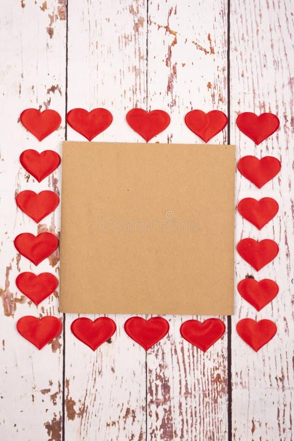 Composição de estilhaços com corações e uma folha de papel sobre fundo de madeira imagens de stock