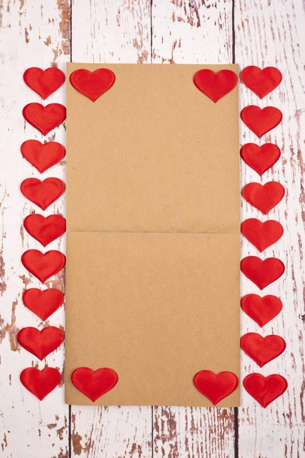 Composição de estilhaços com corações e uma folha de papel sobre fundo de madeira foto de stock royalty free