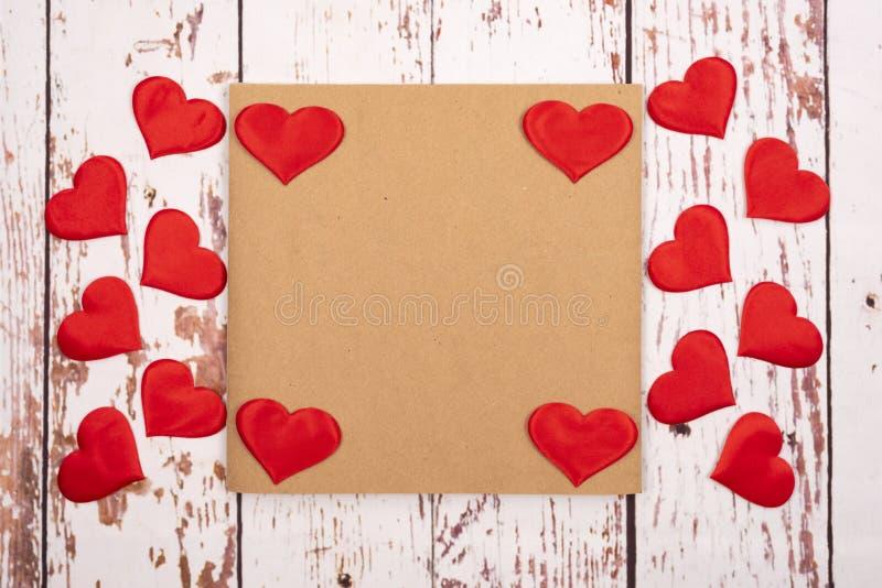 Composição de estilhaços com corações e uma folha de papel sobre fundo de madeira fotos de stock