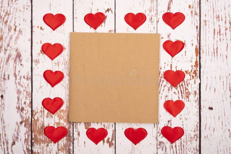 Composição de estilhaços com corações e uma folha de papel sobre fundo de madeira fotos de stock royalty free