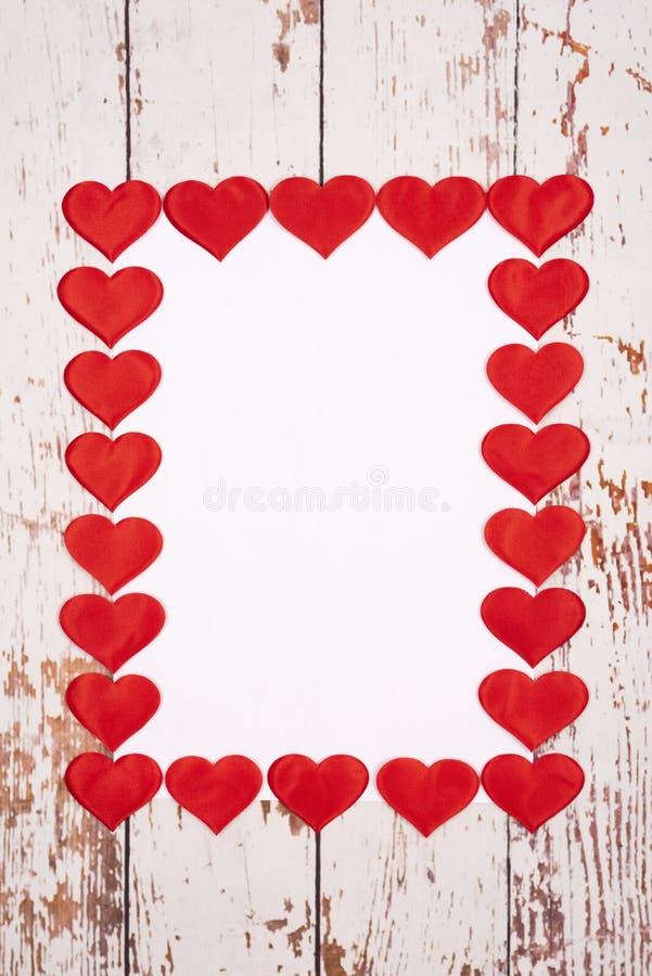 Composição de estilhaços com corações e uma folha de papel sobre fundo de madeira fotografia de stock royalty free