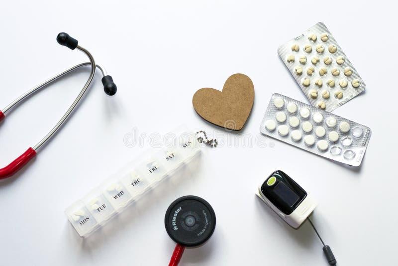 Composição de Flatlay do equipamento médico com coração de madeira no fundo branco Conceito do diagnóstico, tratamento, hospital, fotografia de stock