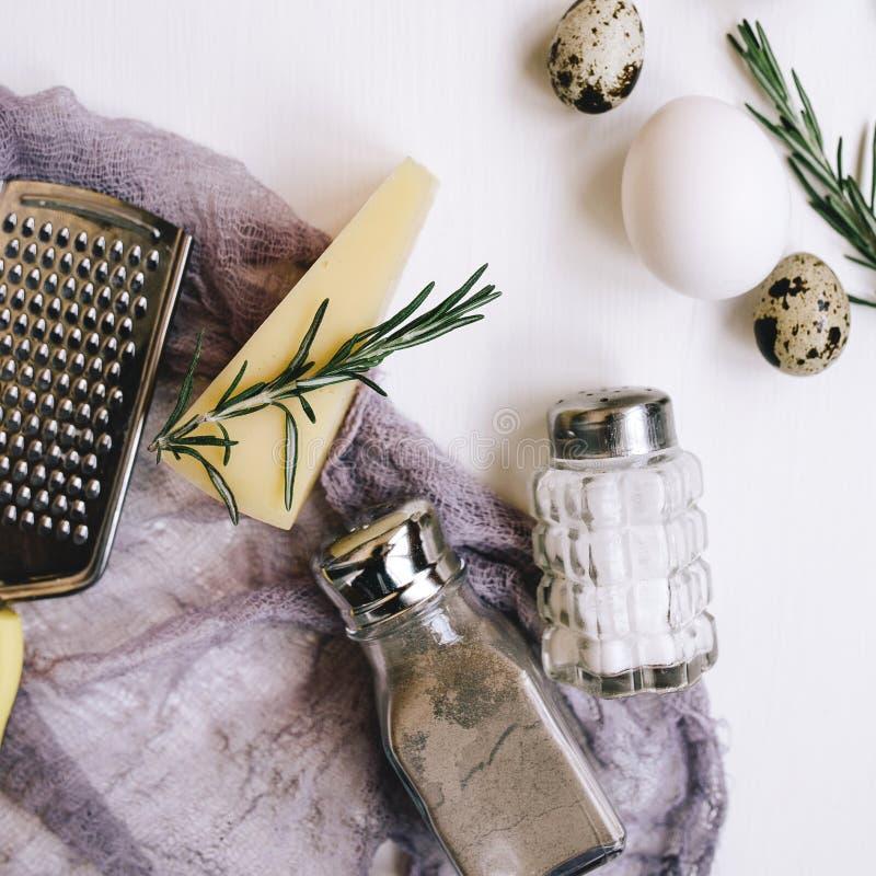 Composição de Flatlay Queijo duro do Parmesão com alecrins, saleiro e pimenta de vidro, ovos e codorniz brancas da galinha, ralad imagens de stock royalty free