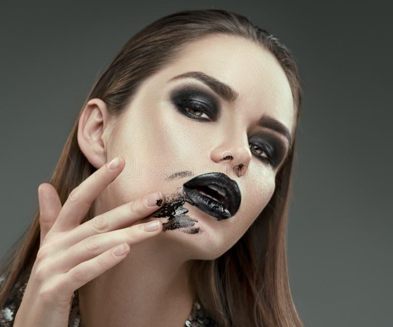 Composição de Halloween Menina do modelo de forma com composição preta gótico na moda A jovem mulher mancha o batom preto em sua  imagem de stock royalty free