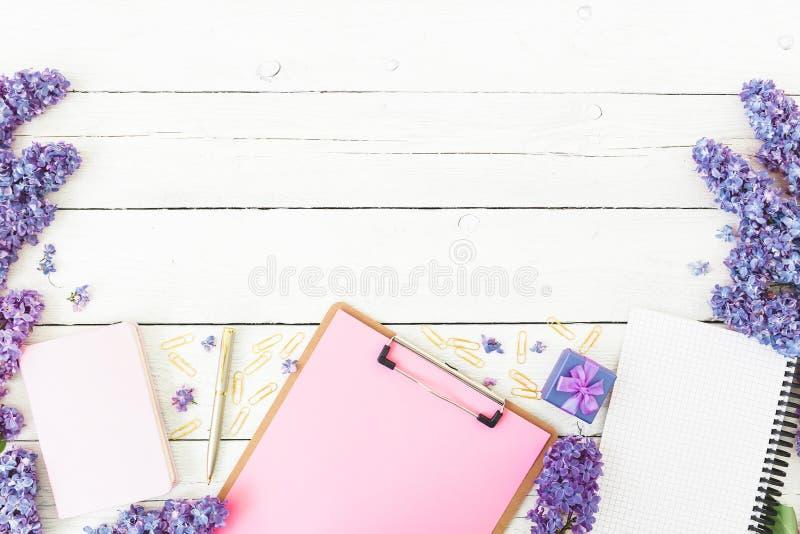 Composição de Minimalistic com prancheta, caderno, as flores lilás, a caixa de presente e os acessórios no fundo de madeira A con fotografia de stock