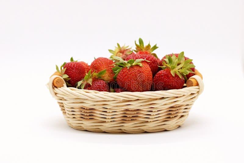 Composição de morangos maduras em um fundo branco em uma cesta de vime fotos de stock