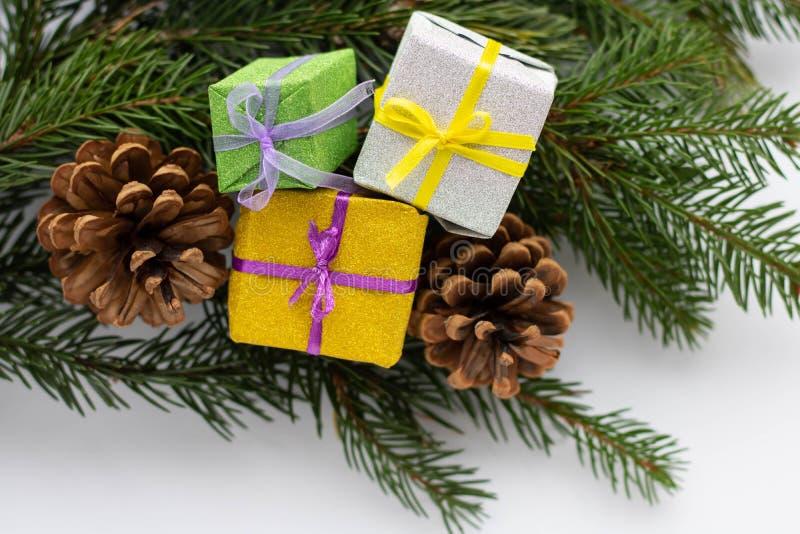 Composição de Natal e Ano Novo Caixa de dotes com ramos de fita e de abetos com cones de fundo branco Posição plana foto de stock royalty free