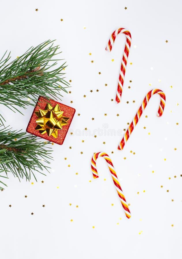 Composição de Natal Ramificação de árvores, caixa de presente vermelha, canhões de doces sobre fundo branco imagem de stock
